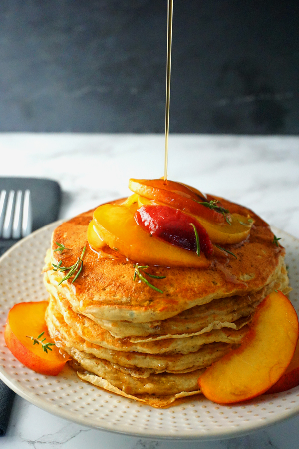 fluffy buttermilk peach pancakes topped with rosemary peach sauce and pure maple syrup
