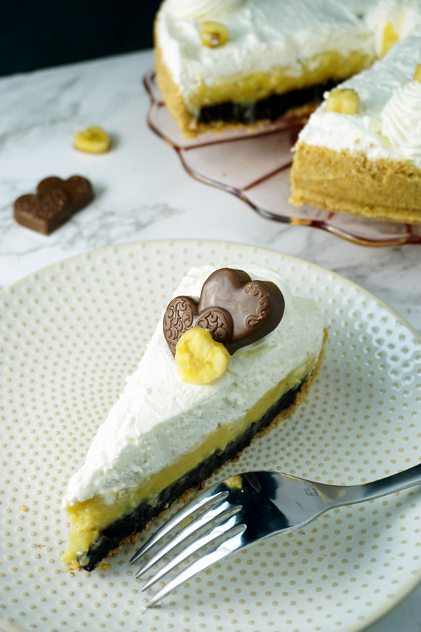 A Slice of black-bottom coconut banana cream pie garnished with a chocolate heart