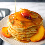 Buttermilk Peach Pancakes drizzled with pure maple syrup