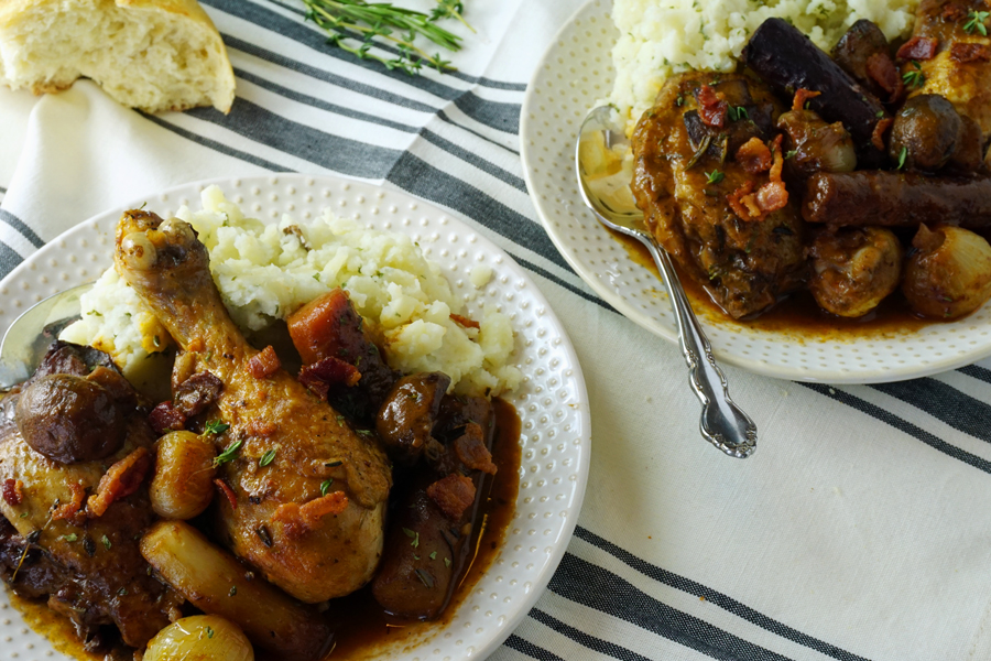 Two plates of Coq Au Vin Chicken served with Mashed Potatoes