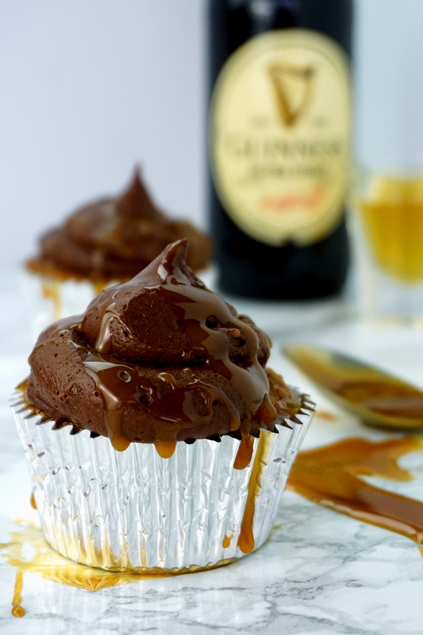 A caramel-flavored cupcake with chocolate buttercream and caramel drizzled on top sits in the foreground of a bottle of Guinness and a shot glass of Jameson Irish Whiskey