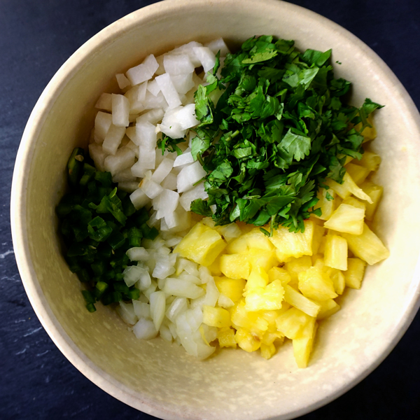 An unmixed bowl of pineapple jicama salsa with cilantro and jalapeno