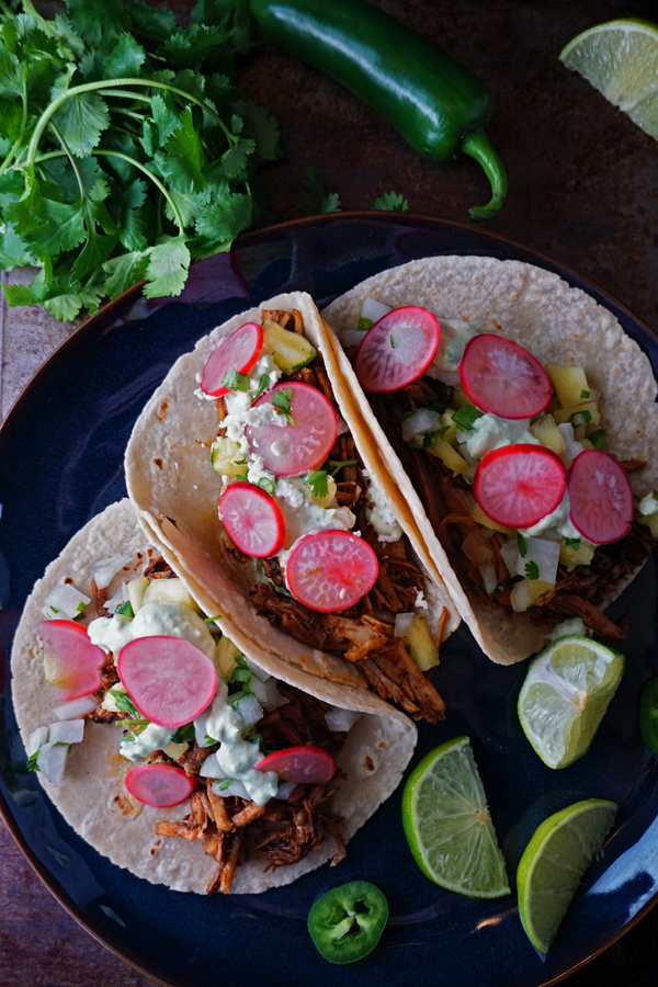 three honey chipotle pork tacos on a blue plate topped with pickled radish and pineapple jicama salsa