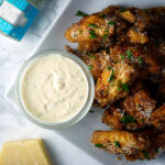 parmesan truffle chicken wings on a plate with garlic dip and a jar of truffle salt
