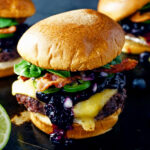 Habanero-lime blueberry compote tops three juicy bacon cheeseburgers