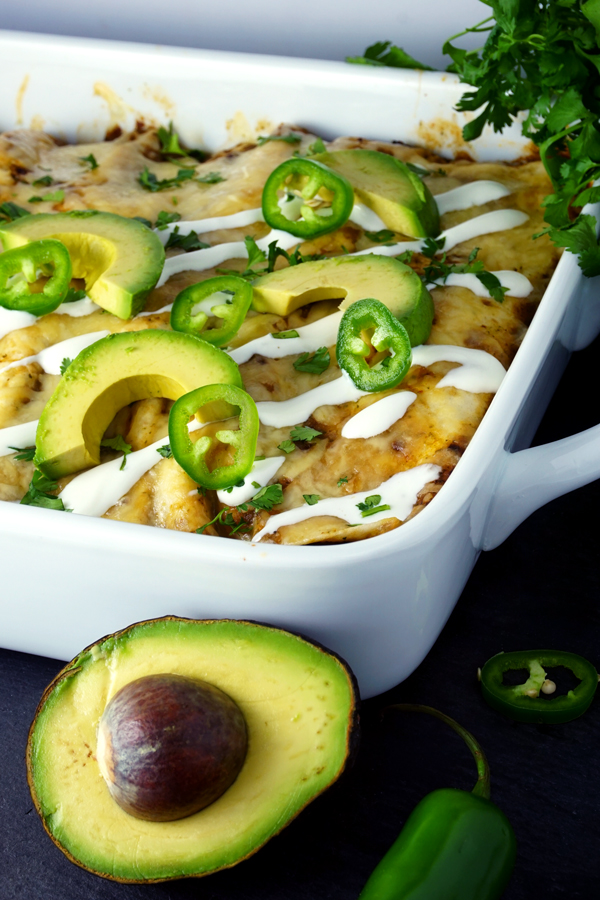 Breakfast enchiladas filled with chorizo and garnished with sour cream, avocado and cilantro
