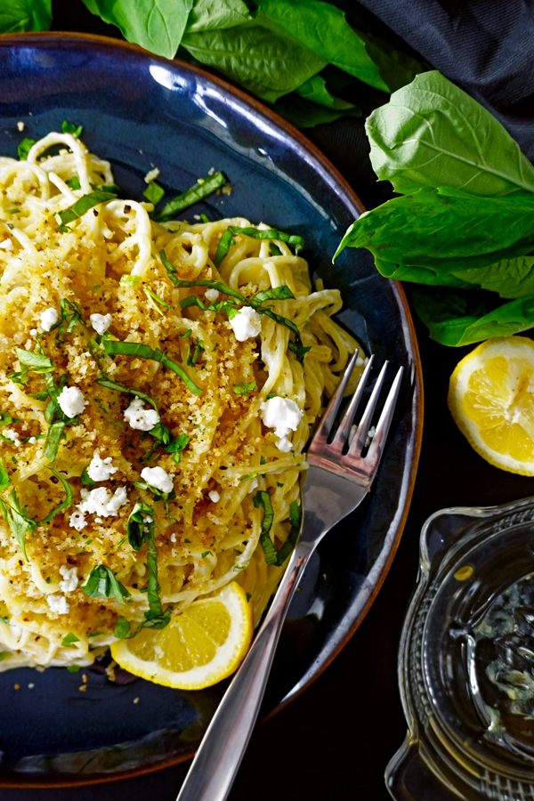 Lemon Goat Cheese Spaghetti with Toasted Pangrattato Breadcrumbs on a blue plate with basil and lemon rinds