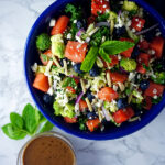 Watermelon kale salad in a blue bowl topped with fresh mint, feta cheese, blueberries, almonds and broccoli with a side of homemade creamy balsamic dressing