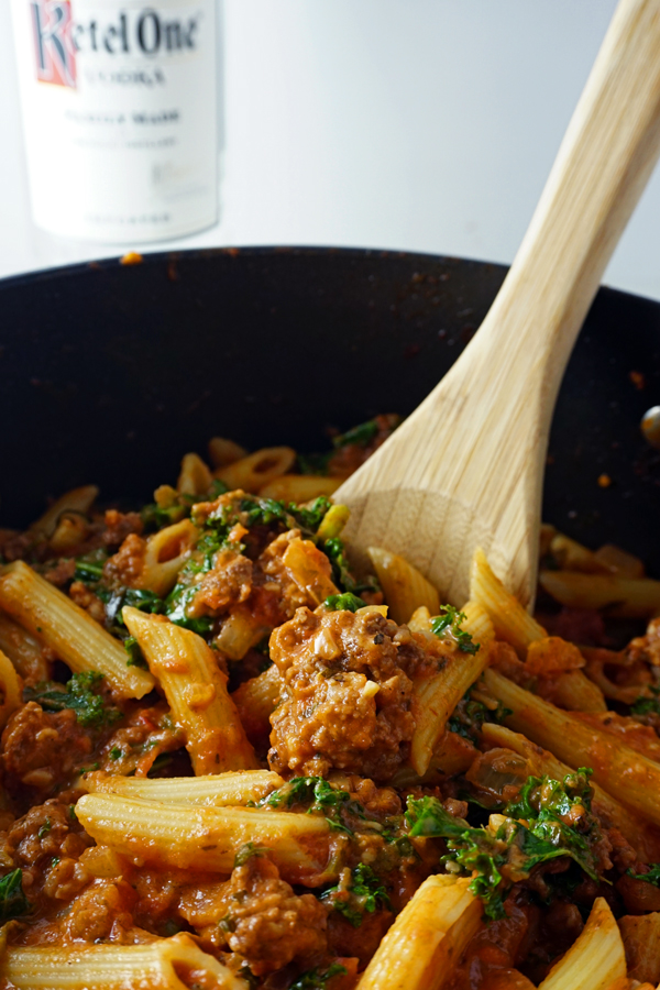 A close-up photo of a wooden spoon stirring penne pasta with creamy vodka sauce