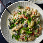 Creamy Gnocchi Soup in a textured bowl with a spoon