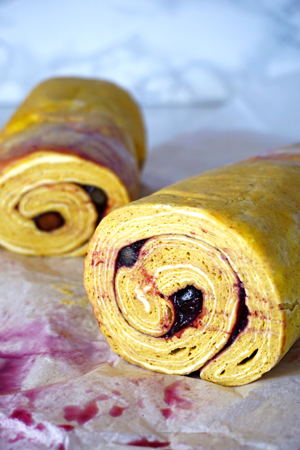 Rolled up laminated morning bun dough filled with blueberries