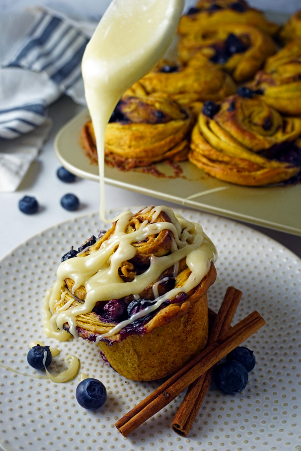 Cream cheese icing being drizzled by a spoon onto a pumpkin blueberry morning bun