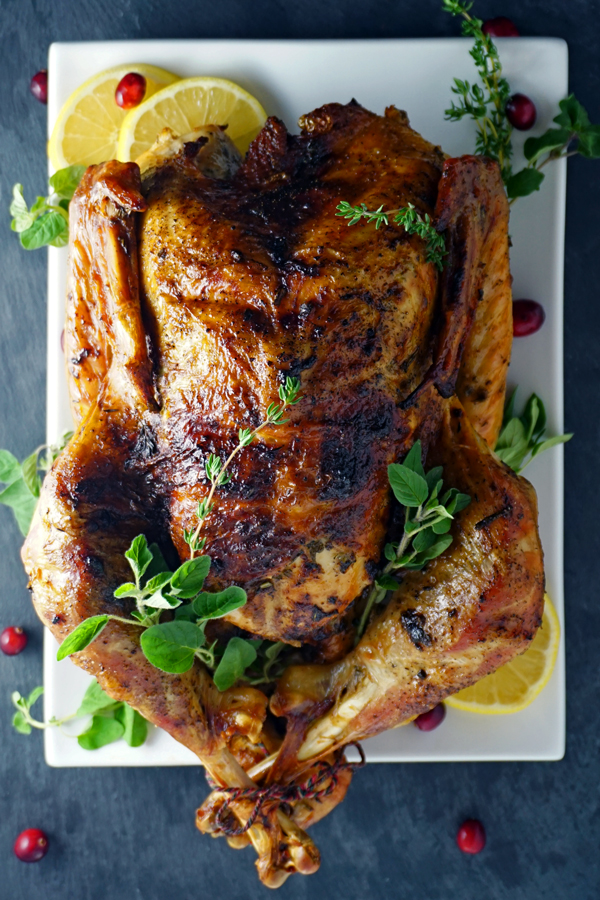 whole mayonnaise-rubbed turkey on a platter with lemon, herbs and cranberries