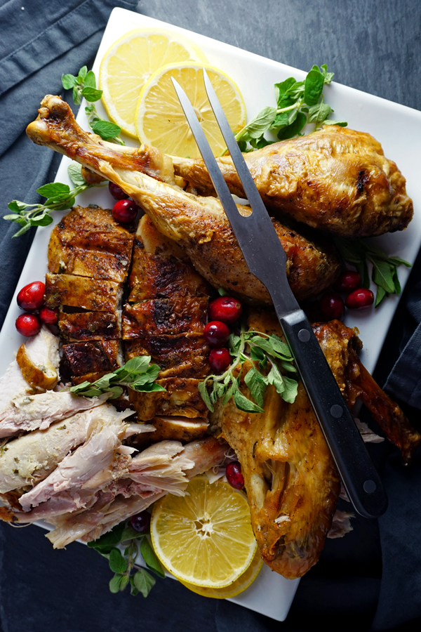 carved mayo-rubbed turkey on a platter with herbs and cranberries