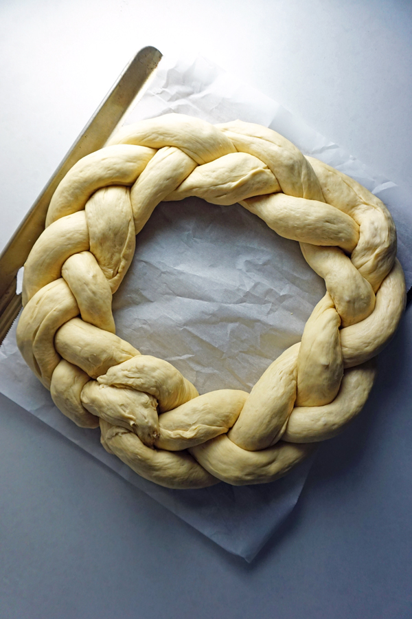 braided pretzel dough shaped into a wreath before baking