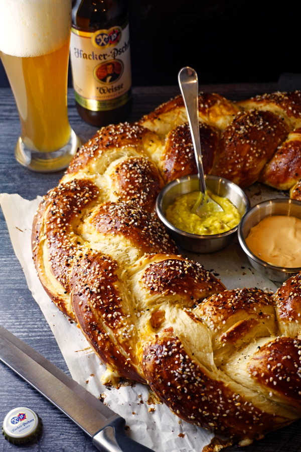 bavarian pretzel wreath with mustard and cheese dips and a german beer