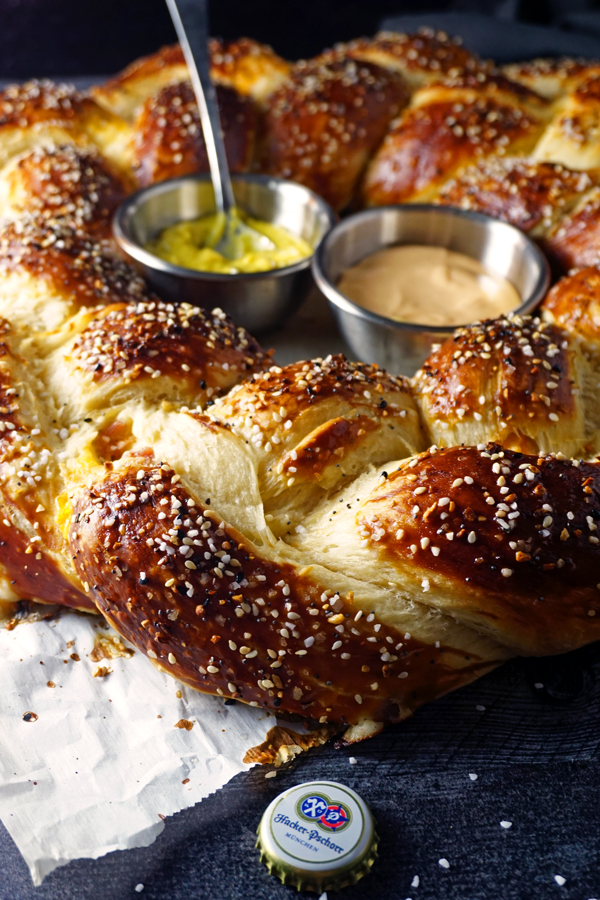 close-up image of braided german pretzel wreath and dipping sauces