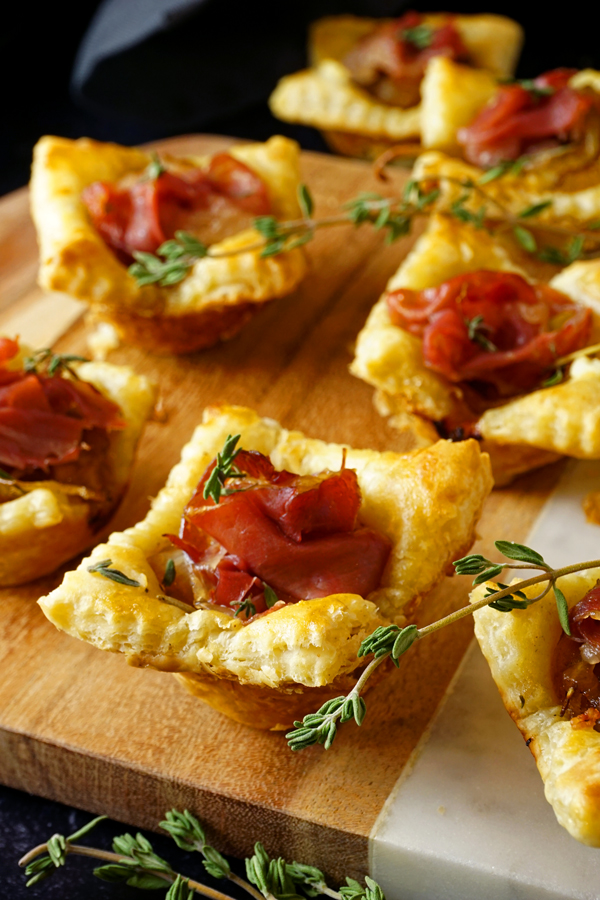 prosciutto-filled caramelized onion tarts on a wood and marble board