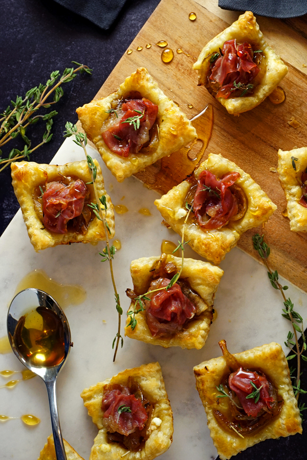 overhead photo of caramelized onion tarts drizzled with honey and filled with prosciutto