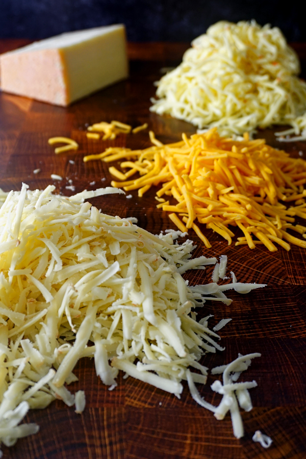piles of grated gruyere, fontina and cheddar cheese on butcher block