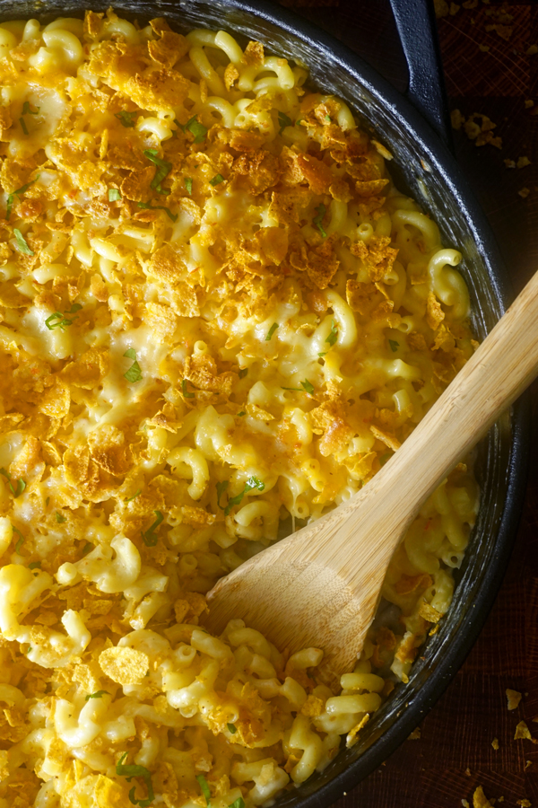 close image of fancy macaroni and cheese with a wooden spoon in it