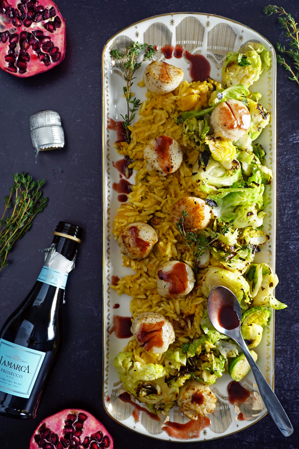 a white and gold platter of jumbo scallops pan-seared with a pomegranate prosecco sauce and served over brussel sprouts and creamy butternut squash orzo