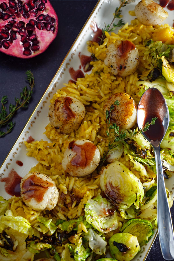 a white and gold platter of pan-seared scallops with a pomegranate prosecco sauce and served over brussel sprouts and creamy butternut squash orzo