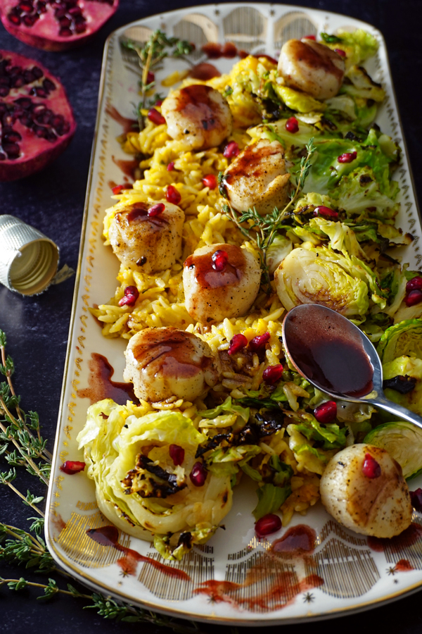 a white and gold platter of sea scallops pan-seared with a pomegranate prosecco sauce and served over brussel sprouts and creamy butternut squash orzo