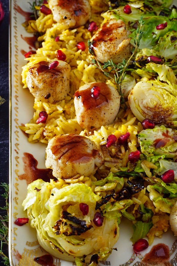 a white and gold platter of scallops pan-seared with a pomegranate prosecco sauce and served over brussel sprouts and creamy butternut squash orzo