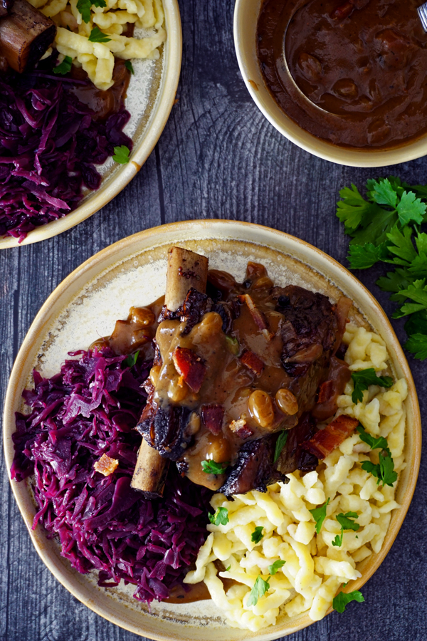 braised beef short ribs prepared as sauerbraten on a plate withred cabbage, gravy and spätzle overhead