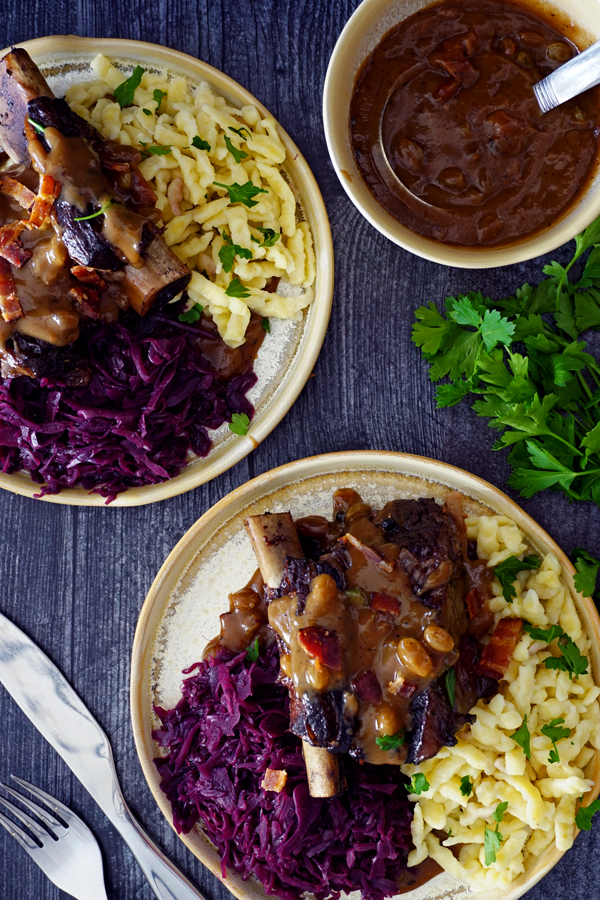 two plates overhead of braised beef short ribs prepared as german sauerbraten with red cabbage, gravy and spätzle