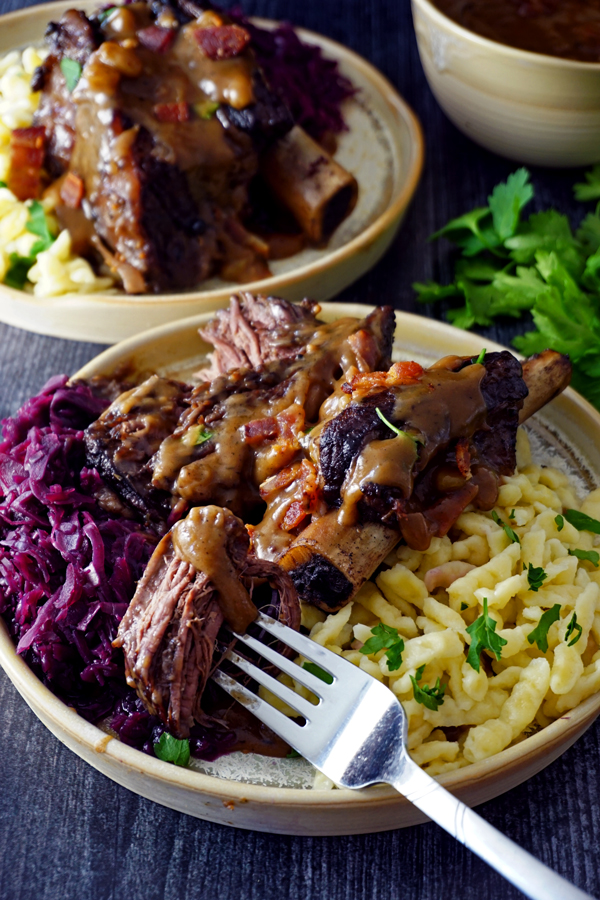 A tender piece of braised sauerbraten short ribs on a fork with red cabbage and gravy