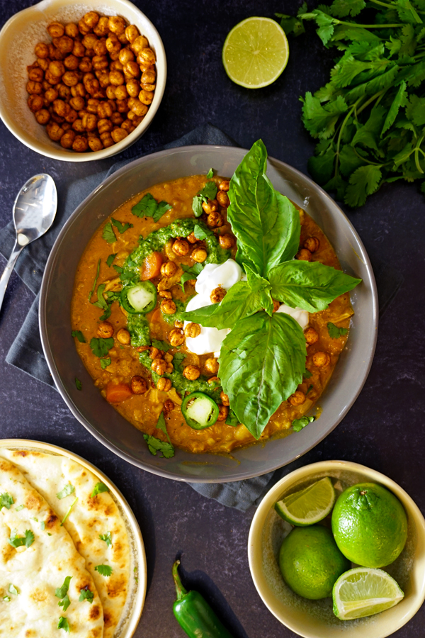 butter chicken soup in a bowl garnished with yogurt, cilantro puree and crunchy chickpeas with limes and naan surrounding it