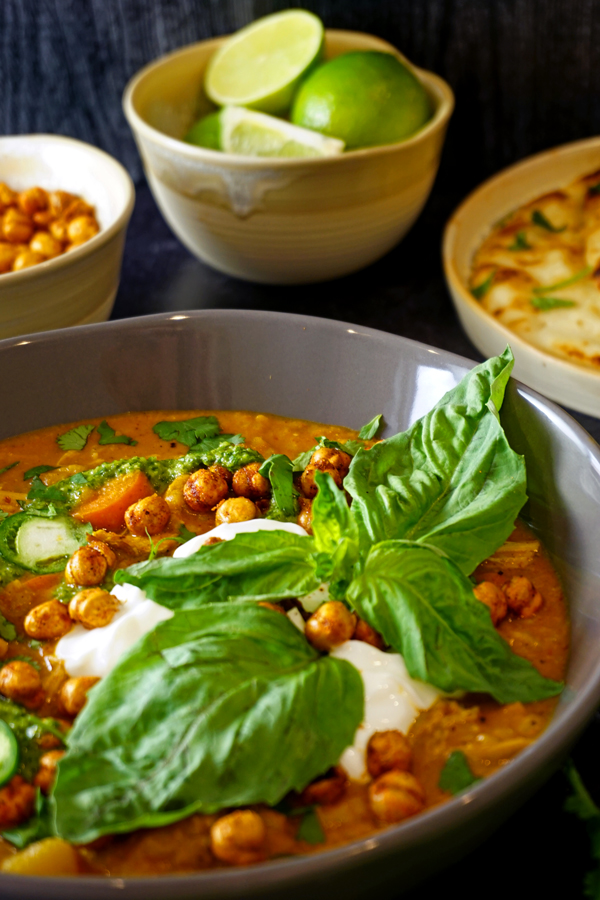 basil leaves and yogurt on an indian curry soup made in the instant pot