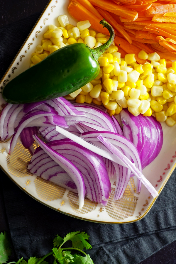 shredded carrots, corn kernels, sliced red onions and a whole fresh jalapeno on a decorative platter
