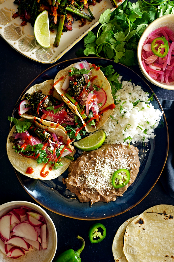 a blue plate with three charred vegetable tacos, rice and beans surrounded by tortillas and other tacos fillings and garnishes