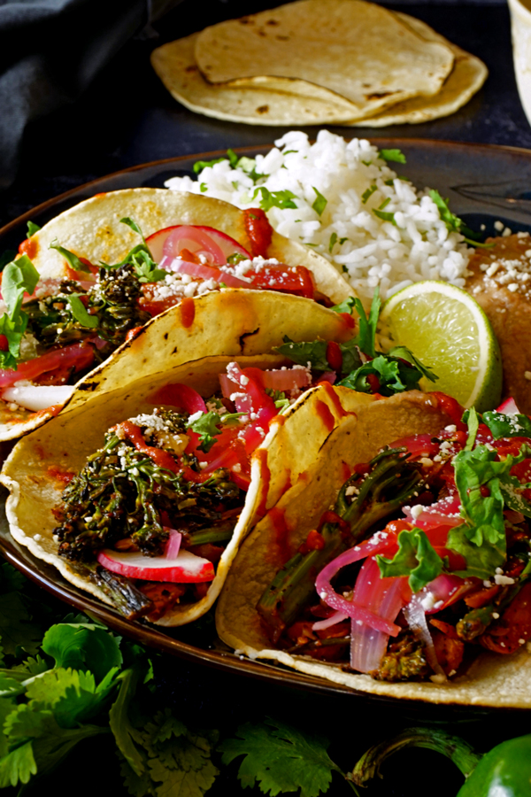 charred vegetables tacos up close on a plate surrounded by cilantro with rice and tortillas in the background