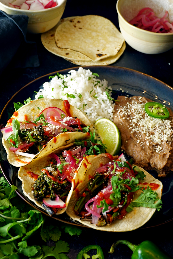 three charred vegetable tacos on a plate with broccolini, radish and cotija cheese and a side of rice and beans