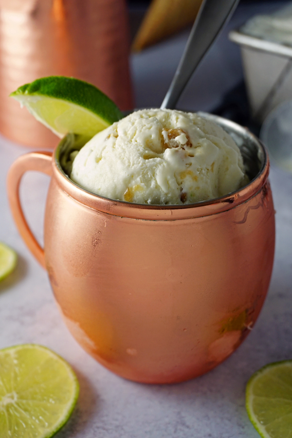 scoops of moscow mule no-churn ice cream in a copper mug, garnished with a lime wedge