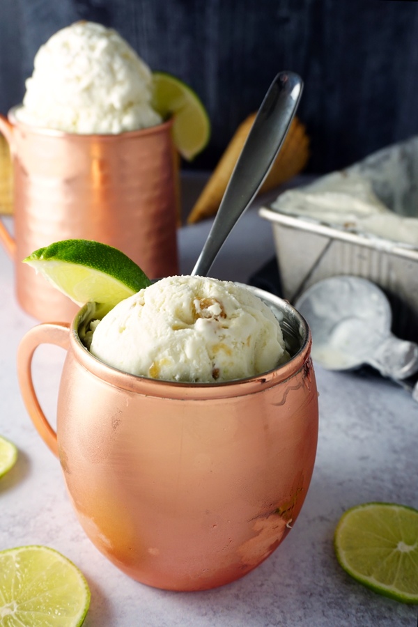 scoops of moscow mule no-churn ice cream in a copper mug, garnished with a lime wedge with another mug and extra ice cream in the background