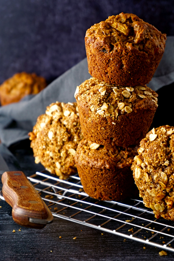 freshly baked morning glory muffins stacked together with a knife on a wire cooling rack